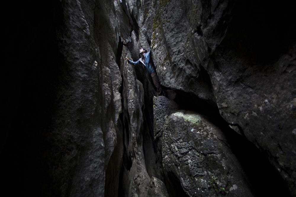 Un touriste grimpe dans la forêt de pierre du Yunnan.