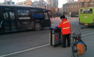 Yu Youzhen  essuie une mince couche de glace formée à la surface de la poubelle en hiver