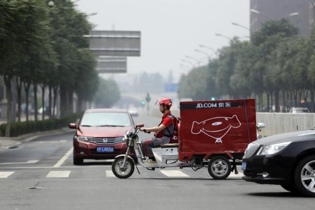 Liu, CEO and founder of China's e-commerce company JD.com, crosses a street on an electric tricycle during a delivery run in Beijing