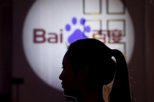 A woman is silhouetted against the Baidu logo at a new product launch from Baidu, in Shanghai, China, November 26, 2015. REUTERS/Aly Song